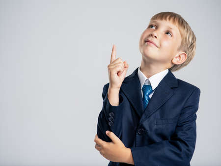 Photo of a  businessman  boy pointing finger up and looking up.  Portrait of white  kid in a blue business suit with an idea. 8 years old child dressed in a business formal suit with tie with an idea.