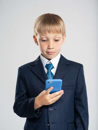 Photo of a shocked businessman  boy with smartphone.  Portrait of a excited  kid in a blue business suit holding a cell phone. Child dressed in a business formal suit with tie looking on smart phone 写真素材