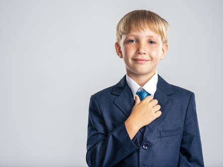 Positive blond boy dressed in a formal suit touching his tie. Portrait of white smiling  kid in a blue business suit looking at camera.  Photo of a happy businessman boy.