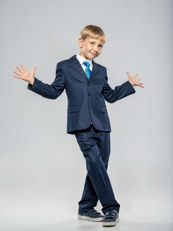 Full portrait of a fun  kid in a blue business suit, posing at studio.   Cheerful boy dressed in a formal suit with blue tie. Photo of  a joyful businessman boy.  Leader conception. Front view 写真素材