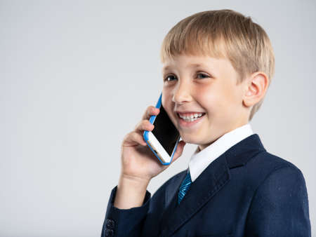 Photo of a  smiling businessman  boy with smartphone .  Happy  kid in a blue business suit holds a cell phone. 8 years old child dressed in a business formal suit with tie talking by phone