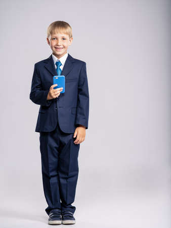 Full portrait of white  kid in a blue business suit holding a cell phone, isolated. Businessman  boy with smartphone . 8 years old child dressed in a business formal suit looking on smart phone.