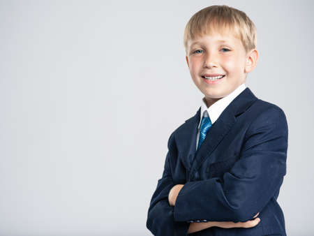 Portrait of white smiling  kid in a blue business suit looking at camera.  Photo of a happy businessman boy.  Positive blond boy dressed in a formal suit with tie with crossed arms on breast