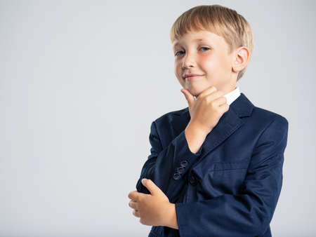 Confident blond boy dressed in a formal suit with blue tie. Portrait of white  kid in a blue business suit, posing at studio.  Photo of a cute little businessman boy.  Leader conception. 写真素材