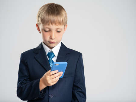 Photo of a  businessman  boy with smartphone .  Portrait of white  kid in a blue business suit holding a cell phone. 8 years old child dressed in a business formal suit with tie looking on smart phone
