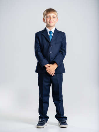 Full portrait of white  kid in a blue business suit, posing at studio.   Confident blond boy dressed in a formal suit with blue tie. Photo of a cute little businessman boy.  Leader conception.