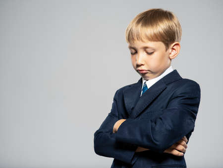 Sad blond boy dressed in a formal suit with blue tie looking down. Upset  kid in a blue business suit, at studio.  Photo of a sad little businessman boy. 写真素材