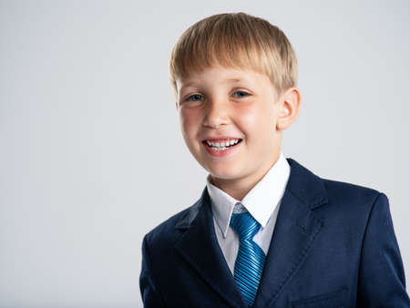 Portrait of white smiling  kid in a blue business suit looking at camera.  Photo of a happy businessman boy.  Positive blond boy dressed in a formal suit with tie, posing at stuido