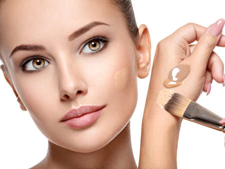Makeup artist applying liquid tonal foundation  on the face of the woman