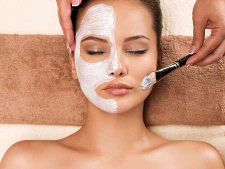 Beautiful young woman having a facial cosmetic mask at spa salon.