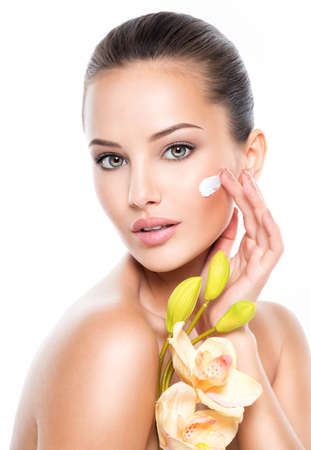 Woman applying cosmetic  cream on a face. Fresh flower on the body 写真素材