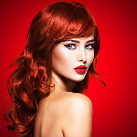 Beautiful sensual woman with long red hair and red nails on red background 写真素材