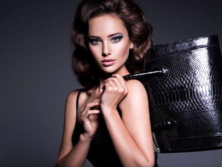 Beautiful sexy woman with brown hair holds black handbag posing at studio