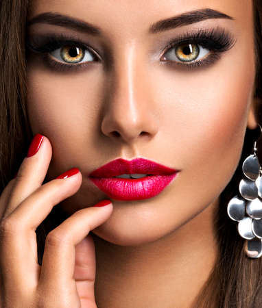 Closeup portrait of beautiful seductive woman with dark brown eye makeup and bright red lips and nails 写真素材