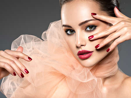 Beautiful  woman with brown  makeup and red nails and lips. Fashion model posing at studio