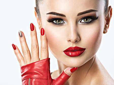 Closeup portrait of beautiful woman with bright fashion make-up and red nails