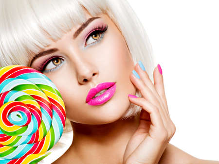 Close-up face of a beautiful  girl with brown eye makeup and bright multicolor nails. Fashion model posing on white background