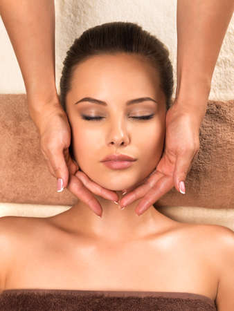 Portrait of beautiful young healthy woman relaxing and getting head massage in the spa salon. 写真素材