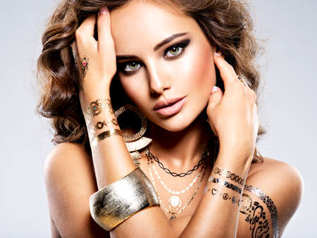 Beautiful Woman  Face Fashion  Jewelry  Make-up. Portrait of young adult sexy girl with brown hair. Golden jewelry. Brown makeup. 写真素材