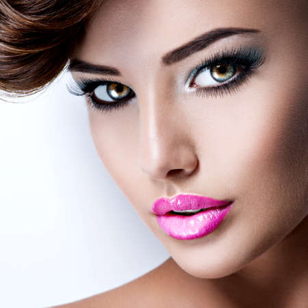 Closeup face of young pretty woman with  beautiful eyes  and bright vivid pink color lipstick 写真素材