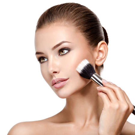 Portrait of a woman  applying cosmetic makeup on the face using makeup brush.