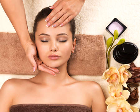 Portrait of beautiful young woman relaxing with head massage at spa salon.