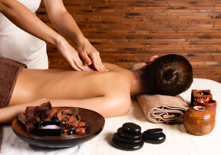 Masseur doing massage on womans back in the spa salon.