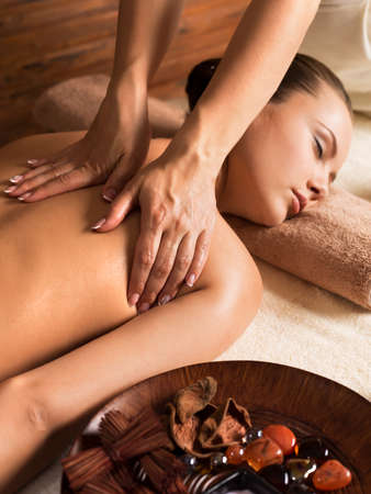 Portrait of beautiful young woman relaxing with back massage at spa salon.