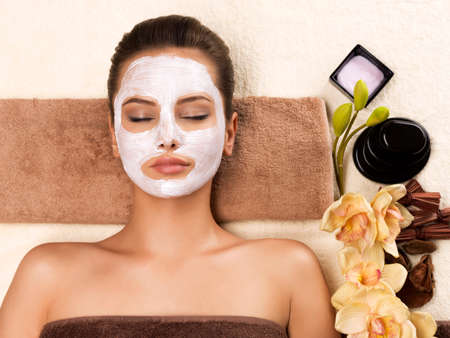Portrait of beautiful young healthy woman with mask on her face relaxing in the spa salon. Beauty treatment concept. 写真素材