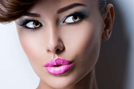 Closeup face of beautiful woman with fashion bright vivid color makeup. Portrait of a pretty girl model with pink lipstick looking away