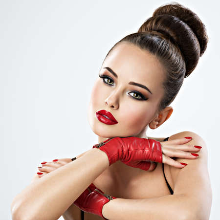 Beautiful sensual woman with glamour makeup. Fashion model with stylish creative hairstyle. Pretty sensual young adult girl in red leather gloves 写真素材
