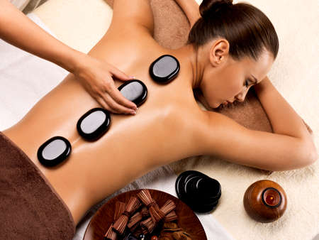Beautiful woman relaxing in spa salon with hot stones on body. Beauty treatment therapy 写真素材