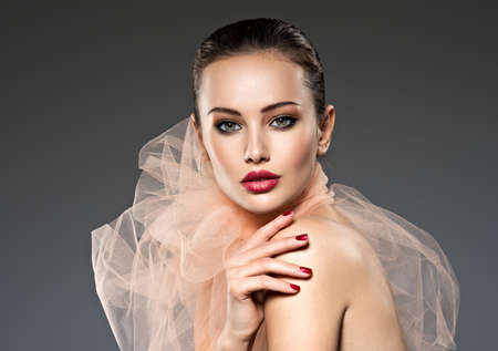 Beautiful  woman with brown  makeup and red nails and lips. Fashion model posing on grey background 写真素材