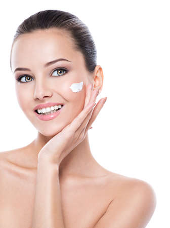 Young smiling woman with cosmetic  cream on a clean fresh face