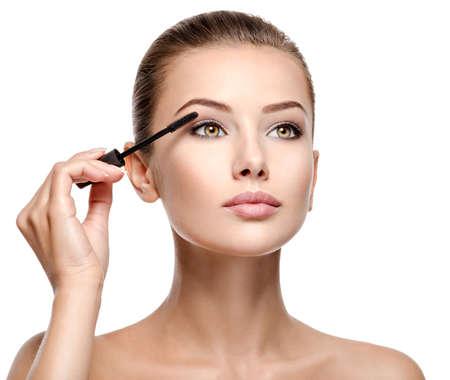 woman applying cosmetic mascara on eyelashes using curling brush - isolated on white