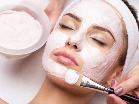 Young beautiful woman receiving  facial mask in spa beauty salon 写真素材