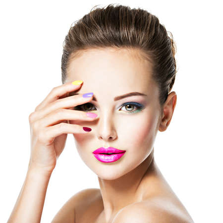 Close-up face of a beautiful woman  with colored nails and pink lips .