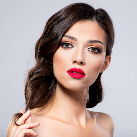 Beautiful young fashion woman with red lipstick.  Brunette woman with a clean skin of face. Portrait of model with bright red lips. Glamour fashion model with bright gloss make-up  posing at studio.