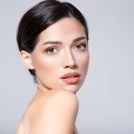 Beautiful face of young woman with health fresh skin. Portrait of beautiful brunette woman with clean face. Beautiful face of young adult woman with clean fresh skin - isolated on white. Skin care.