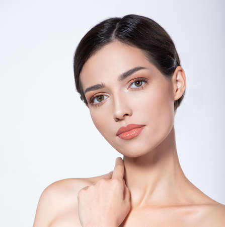 Portrait of beautiful brunette girl which touching her fresh face. Beautiful face of young woman with health fresh skin. Beautiful face of young adult woman with clean fresh skin. Skin care. Stockfoto