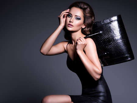 Beautiful woman with long hair in dress with black handbag posing at studio Фото со стока