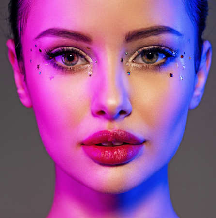Portrait of the girl is highlighted in bright blue and purple light. Face of a beautiful model. Colorful portrait of a girl with bright makeup. Shiny sequins on the face. Art portrait. Sexy woman. Archivio Fotografico