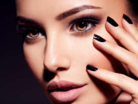Face of a beautiful girl with fashion makeup and black nails posing at studio over dark background Imagens