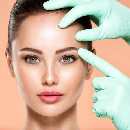 Face skin check before plastic surgery. Beautician touching young woman face. Doctor in medicine gloves checks a skin before plastic surgery. Beauty treatments. Colorful image