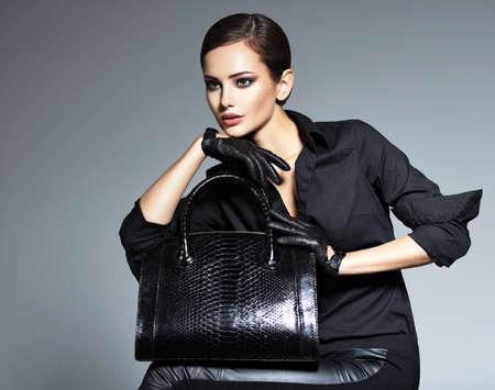 Beautiful woman in black  holds fashion handbag posing at studio