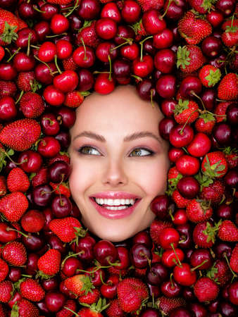 Young, smiling girl with bright makeup and a berry background. Close up of a happy, beautiful caucasian woman with a vivid background. Attractive woman with white, shiny teeth and cosmetics.