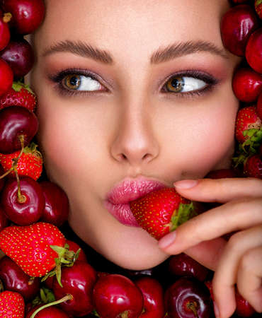 Young girl with bright makeup and a berry background. Beautiful caucasian woman biting a berry. Attractive woman tasting cherry and strawberry. Beautiful woman with fashion makeup and a vivid background.