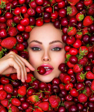 Young girl with bright makeup and a berry background. Beautiful caucasian woman biting a berry. Attractive woman tasting cherry. Beautiful woman with fashion makeup and a vivid background.