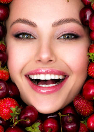 Young, laughing girl with bright makeup and a berry background. Close up of a happy, beautiful caucasian woman with a vivid background. Attractive woman with white, shiny teeth and cosmetics. 版權商用圖片