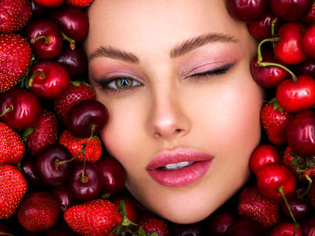 Young, winking girl with bright makeup and a berry background. Happy beautiful caucasian woman.. Attractive close up of a woman's face with a vivid background.